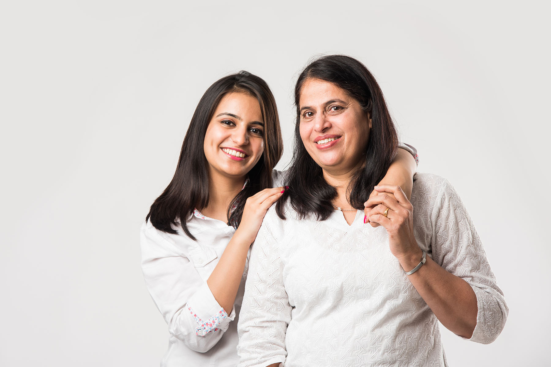 Indian old mother with young Daughter standing isolated over white background, while wearing white top and blue jeans. selective focus